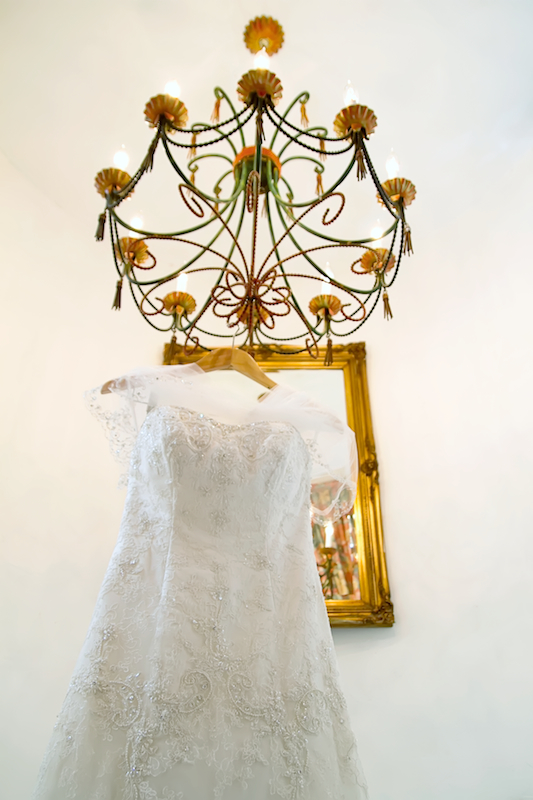 Rancho Las Lomas wedding dress hanging from chandelier with mirror