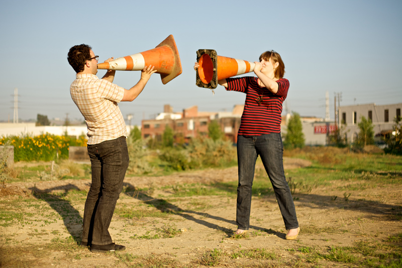 Quirky fun engagement photos with cool hipster couple playing with traffic cones