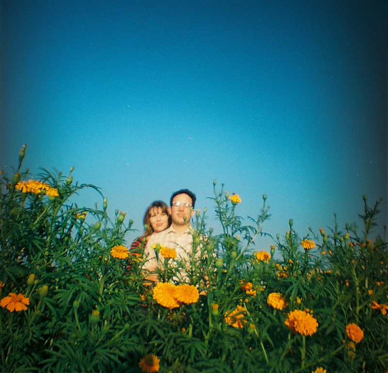 Retro photography of indie couple with orange flowers and blue sky in field