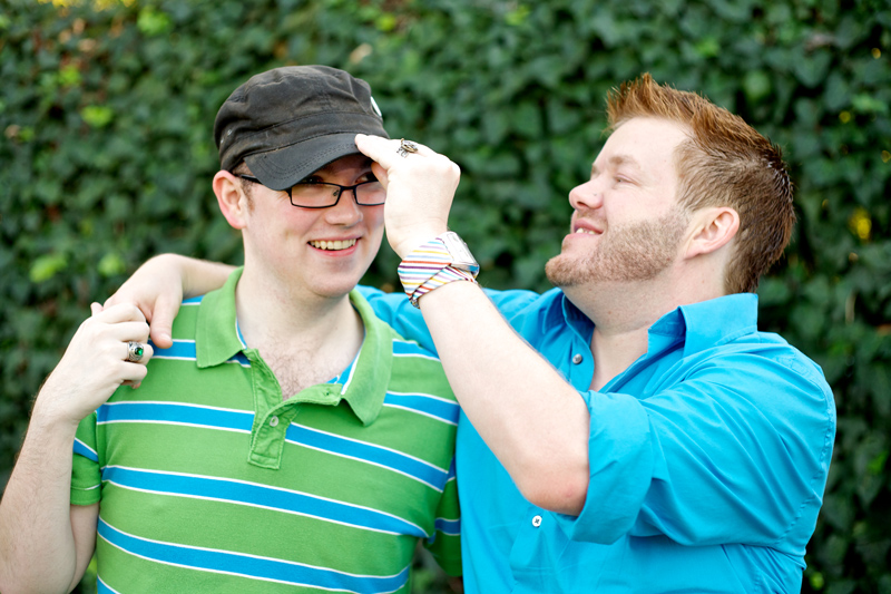Quirky fun engagement photography with cute gay couple playing with hat in park