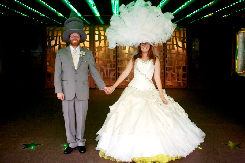 Offbeat bride and groom with funny top hats and feather headdress at cool artsy Los Angeles wedding