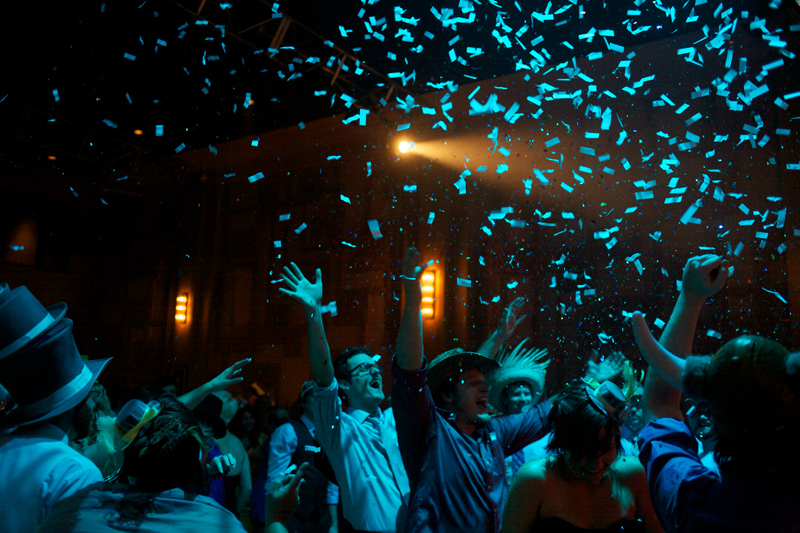 Awesome wedding photography shot of confetti over guests at badass offbeat reception