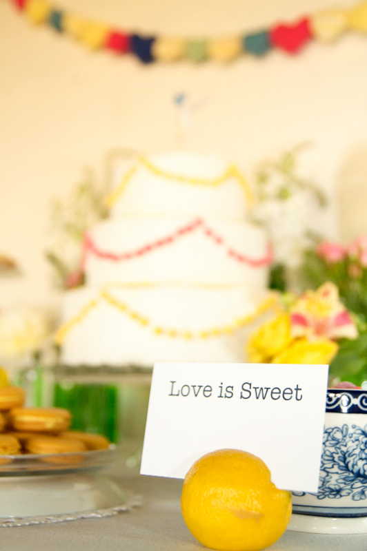 Cool artistic styled photograph of Love is Sweet sign on dessert buffet with wedding cake in the background
