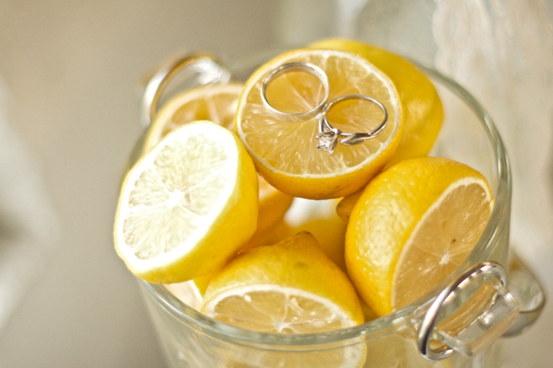 Cool details shot of wedding rings on sliced lemons at yellow wedding