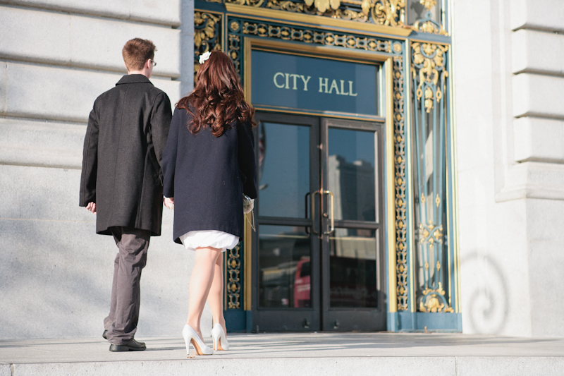 Cute indie couple walking into San Francisco city hall for courthouse elopement