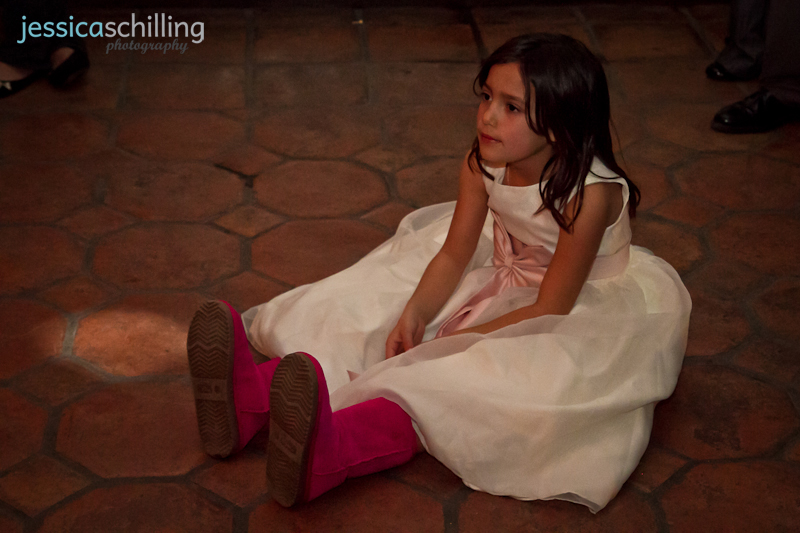 Documentary photography of sweet tired flower girl sitting down on dance floor during wedding reception