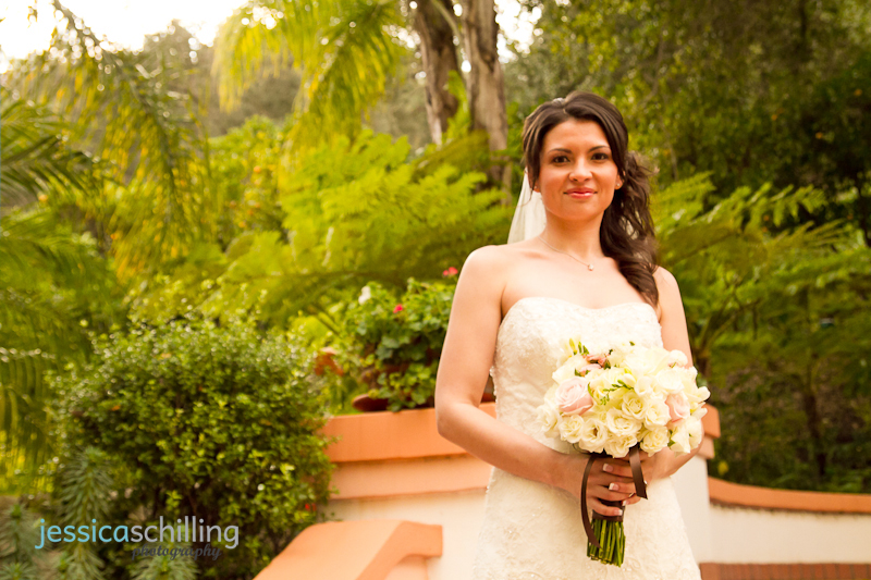 Warm natural light outdoor bridal portraits of bride in dress with bouquet and trees in background