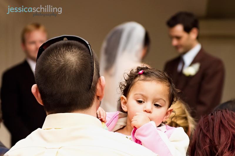 Documentary photojournalist indie wedding photographer baby portrait during ceremony prayer