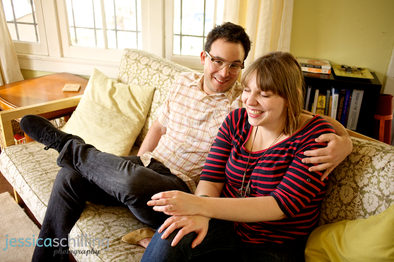 Quirky funny couple laughing during candid, natural living room engagement photos
