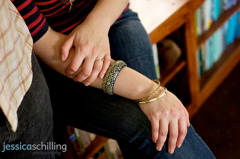 Detail shot of cute bangle bracelets and green diamond engagement ring during portrait photos in living room