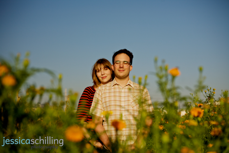 Modern artistic engagement photos in Los Angeles with orange flowers and blue sky
