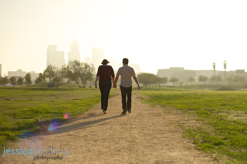 Indie couple walking towards downtown LA skyline in afternoon sunlight