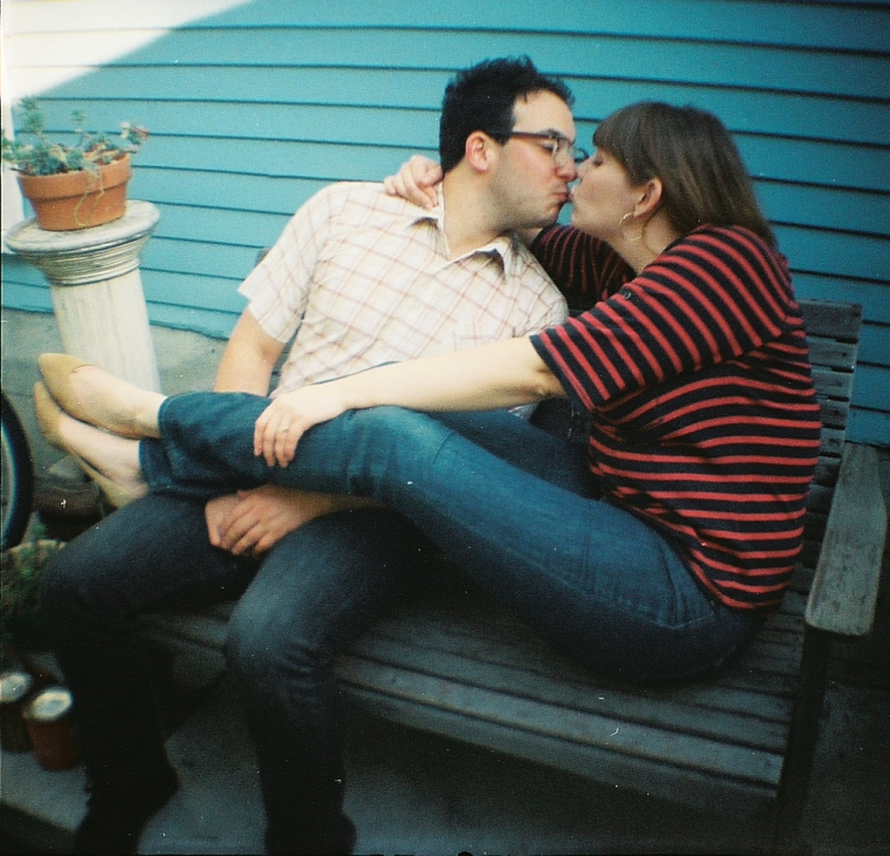 Diana Mini film engagement photo of quirky couple kissing in front of turquoise wall