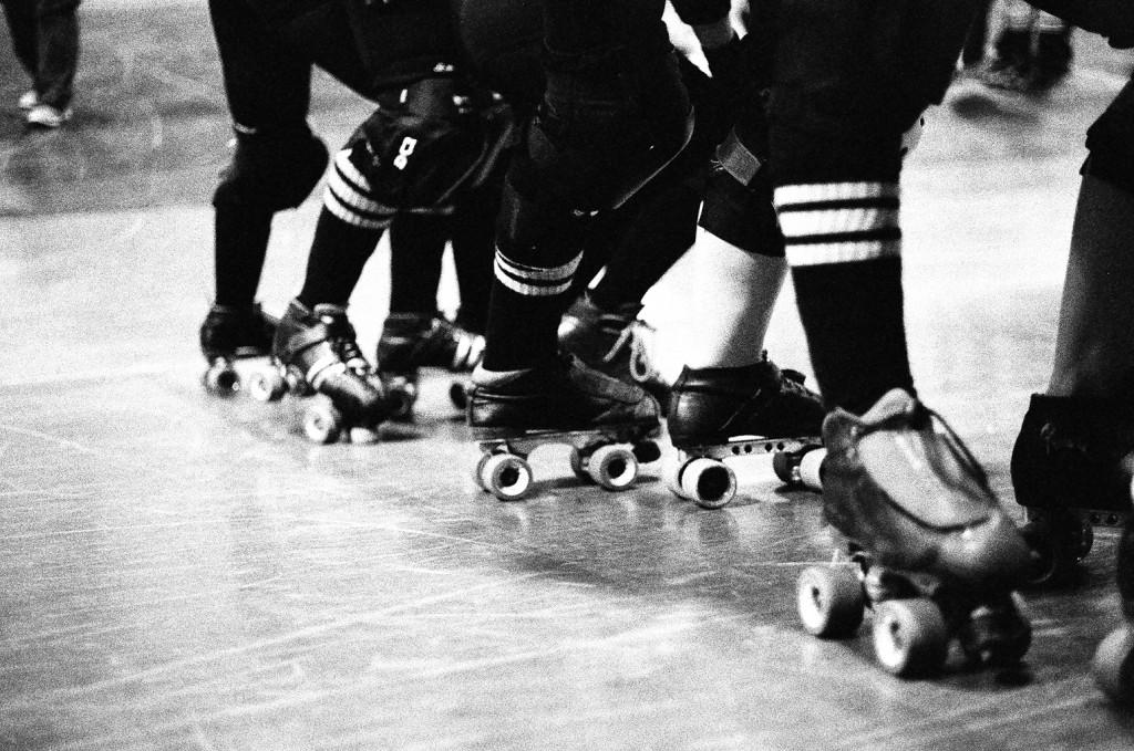 Artistic black and white 35mm film shot of roller derby skates on banked track jam line