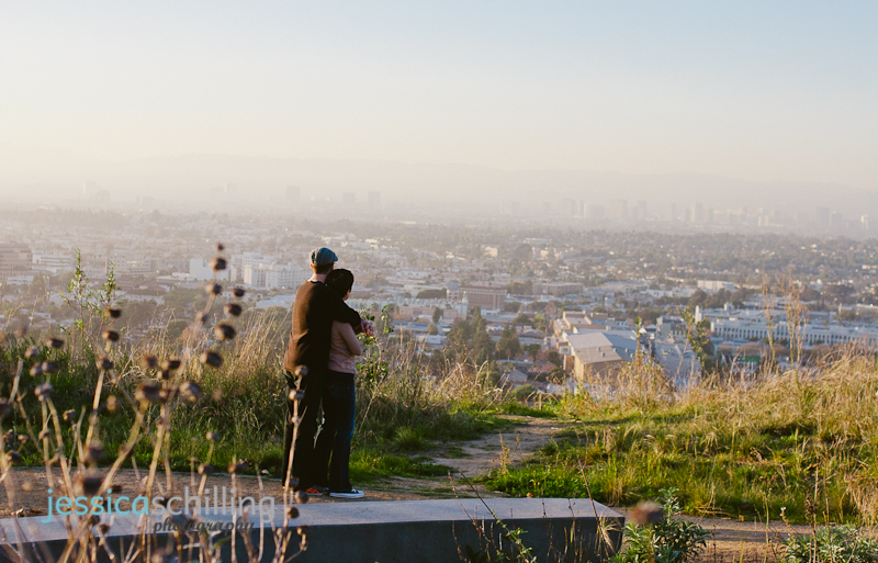 Los Angeles city view with couple looking out from mountaintop during engagement photo session