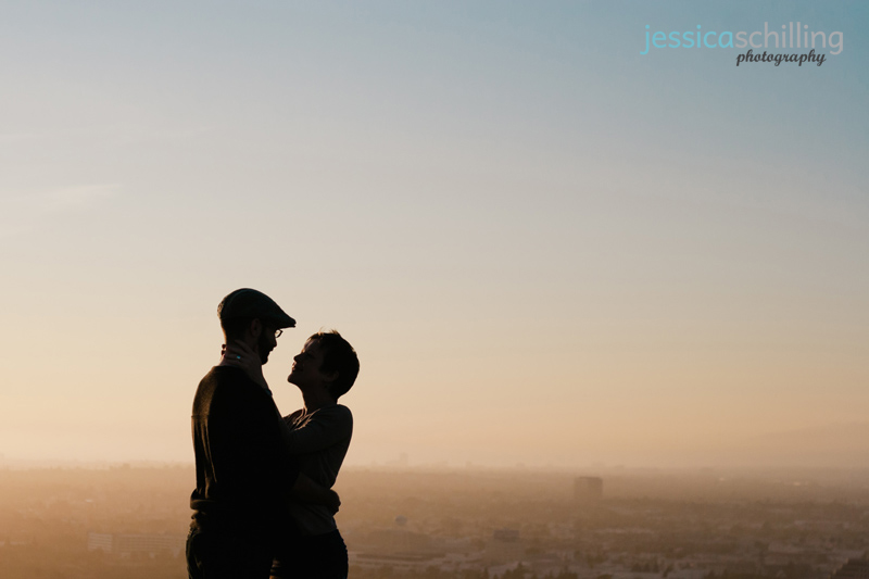 Modern dreamy vintage looking silhouette of couple at sunset overlooking Los Angeles from hilltop