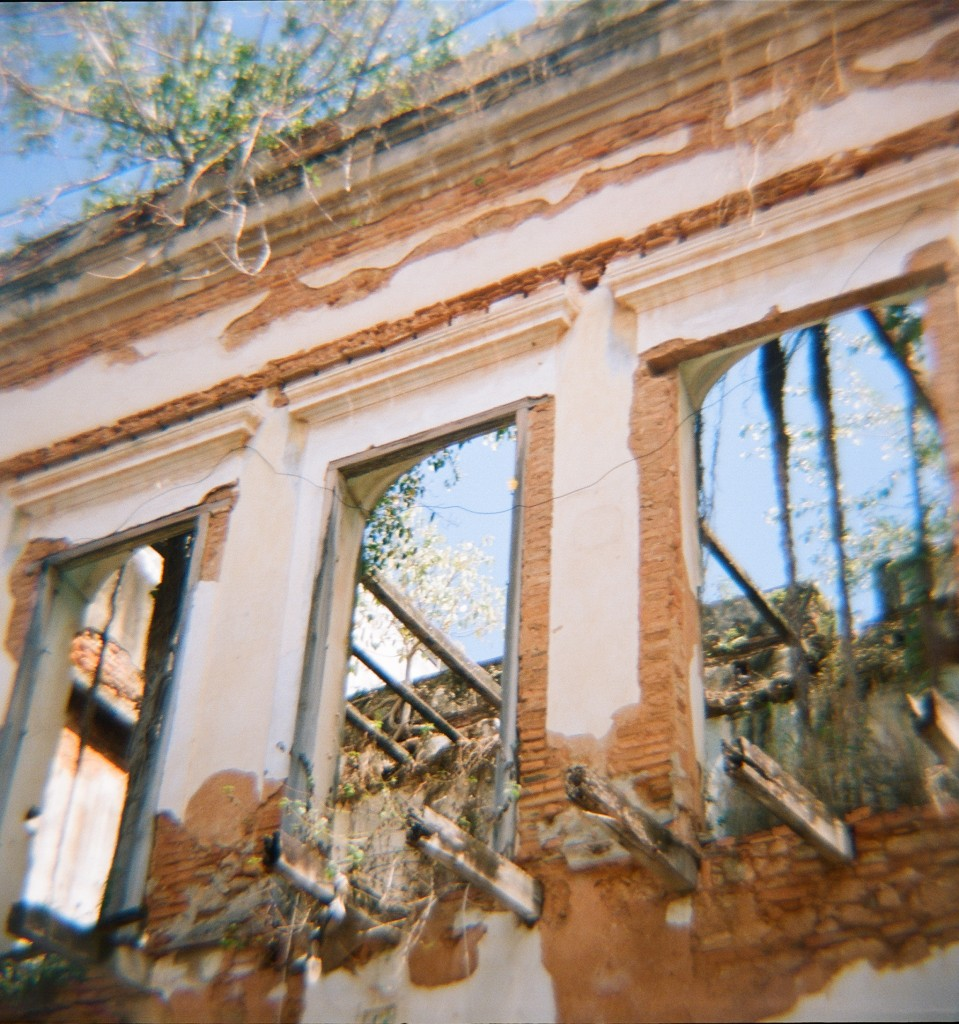 Old San Juan Puerto Rico rundown building without a roof and open windows by Jessica Schilling