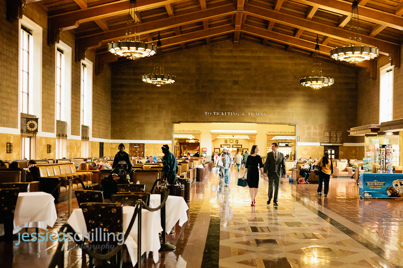 Couple walking through gorgeous art deco train station for vintage-inspired engagement photos