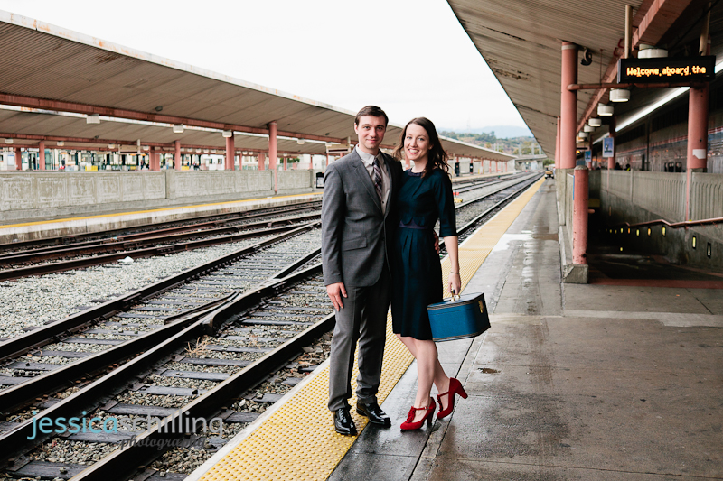 Cute indie couple stand on train platform near tracks for vintage travel themed engagement photos