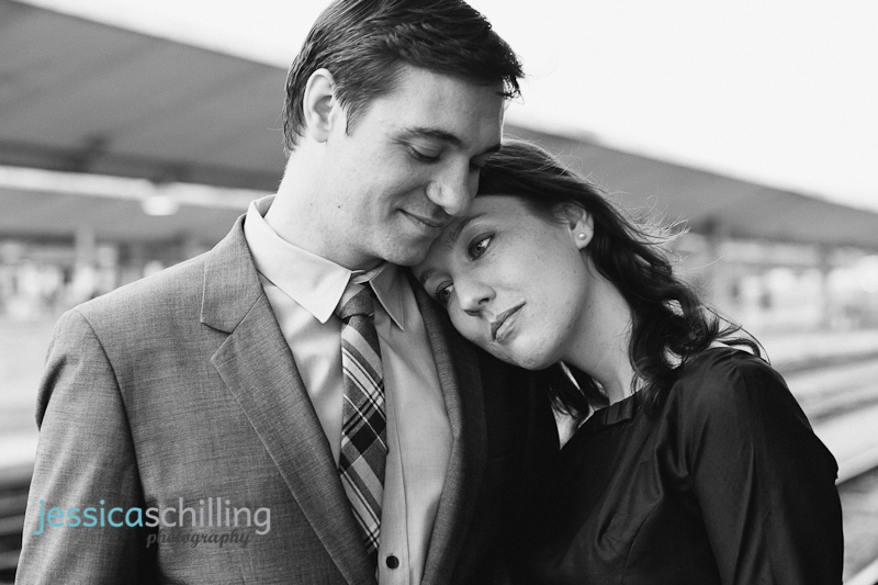 Sweet moment of couple standing on train platform in black and white
