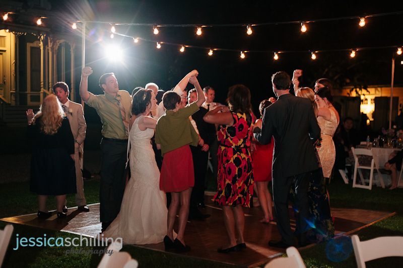 couple and guests dance to &quot;Don't Stop Believin&quot; at wedding reception