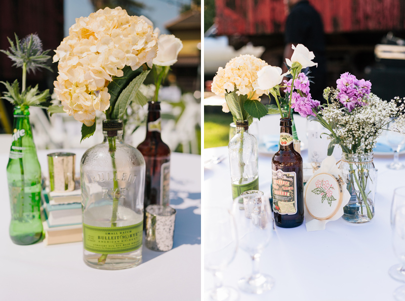 vintage soda and liquor bottles as vases for simple antique table scapes