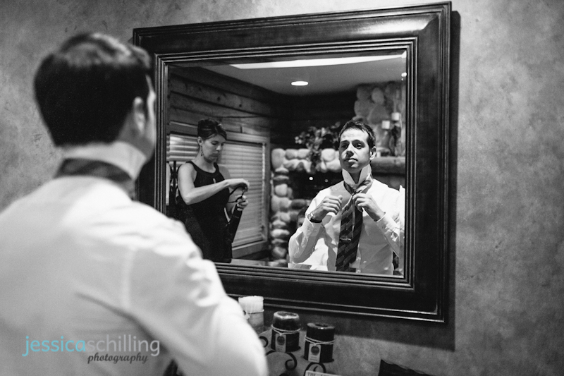 modern black and white wedding photography with groom putting on tie