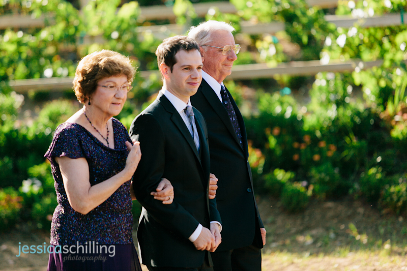 Groom walking down aisle with parents at Temecula wedding