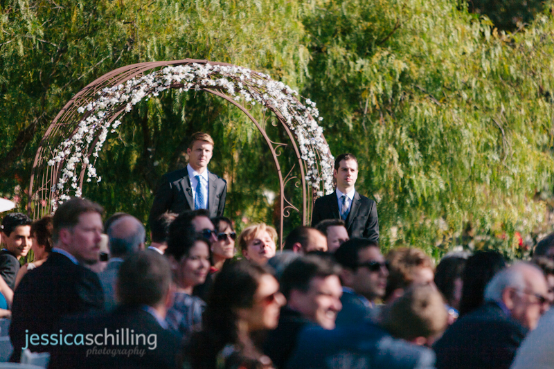 Groom waits to see bride first time at outdoor wedding ceremony