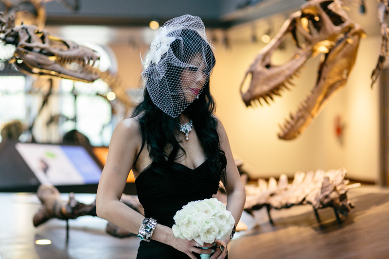 offbeat bride in goth black wedding dress with dinosaurs