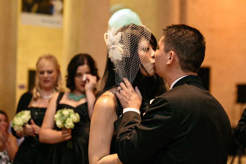 offbeat bride and groom kiss at dinosaur wedding