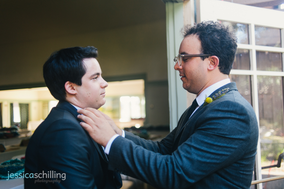 groom pinning bout on brother groomsman at Eagle Rock indie wedding