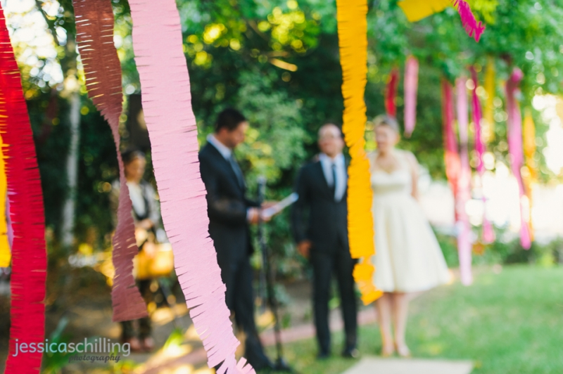 Colorful paper streamers garlands hanging from trees for outdoor wedding ceremony decor