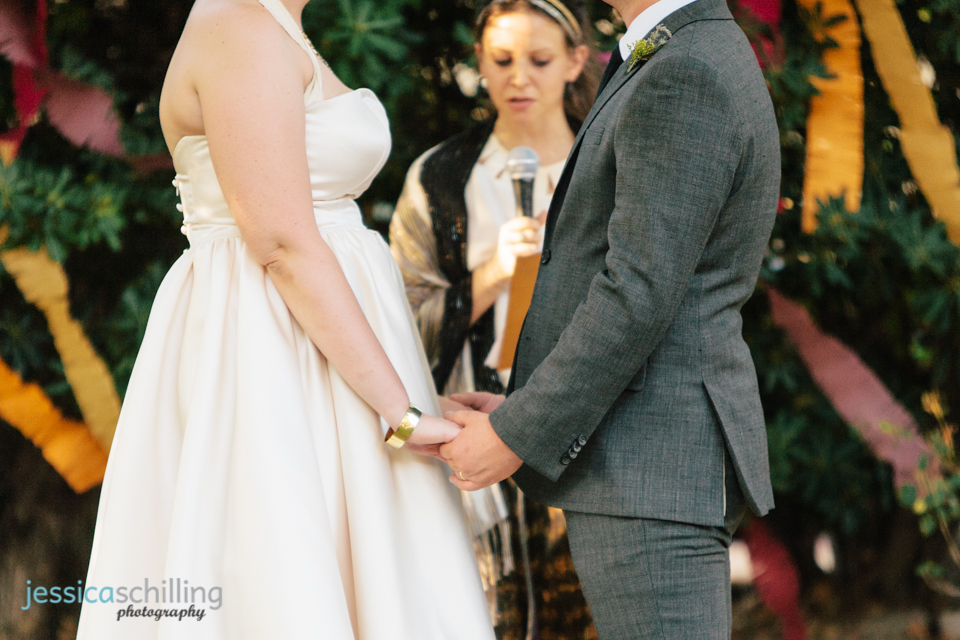 bride and groom hold hands at indie wedding ceremony Los Angeles