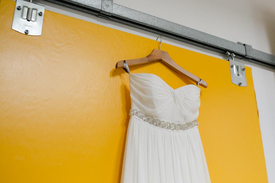 LA bridal gown hanging from industrial chic yellow door