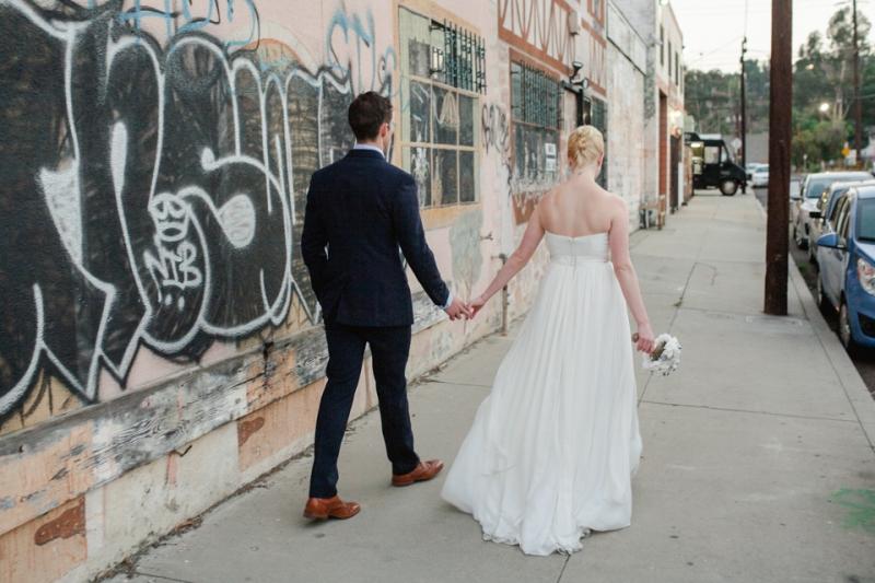 Los Angeles bride and groom walk past graffiti in urban neighborhood at Elysian LA