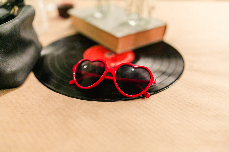 Bride's red heart shaped sunglasses on top of vinyl record at wedding reception