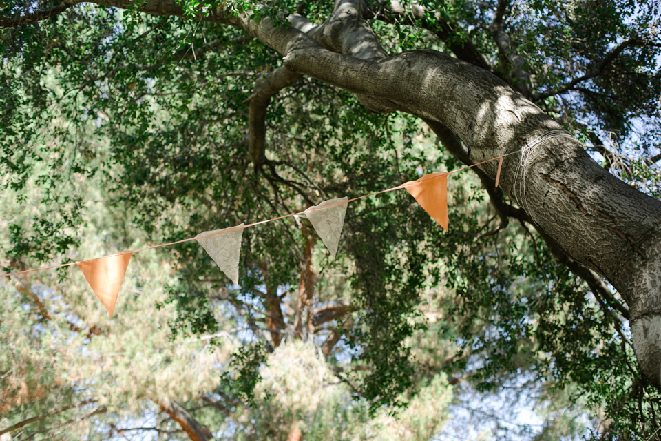 DIY peach lace and fabric bunting banner hanging from oak tree at outdoor wedding ceremony