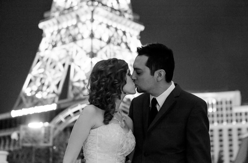 bride and groom kiss in front of Eiffel Tower at night