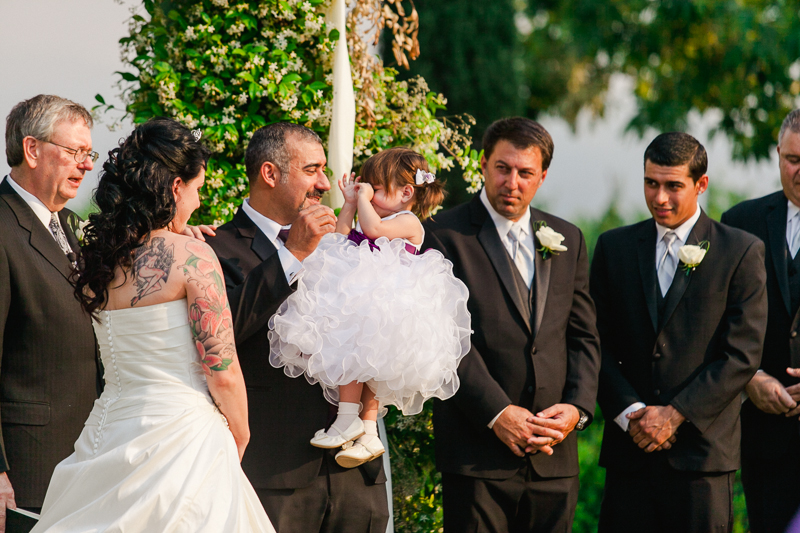 Bride, groom, and daughter during intimate ceremony moment