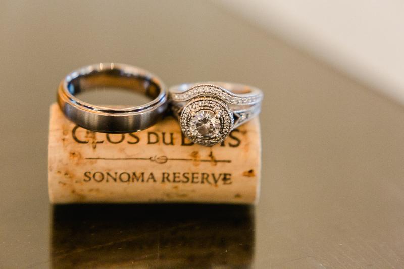 bride and groom wedding rings on wine cork at vineyard wedding