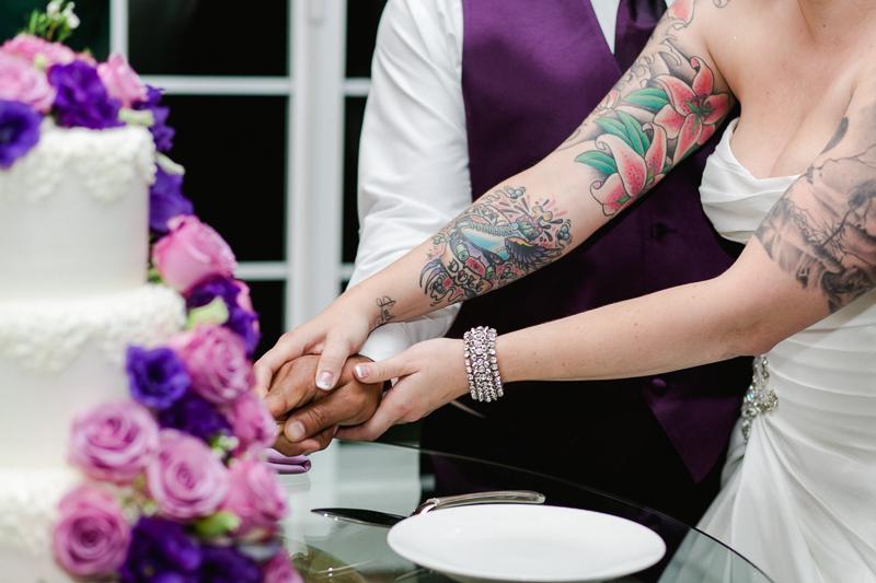 Offbeat tattooed bride cuts cake at vineyard wedding