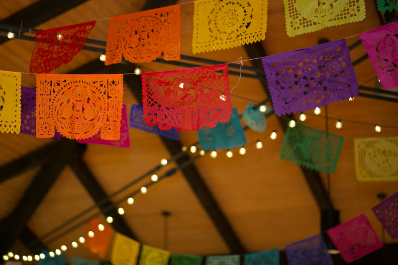 Papel Picado colorful flag bunting at modern Jewish meets Mexican fiesta wedding