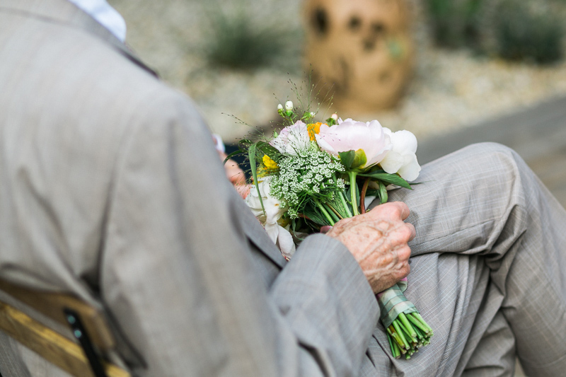 Father of bride holding her bouquet during wedding ceremony