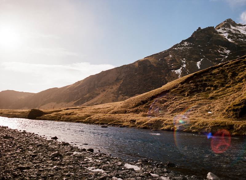 Iceland destination travel photography. Lens flare on film at Skogafoss waterfall.