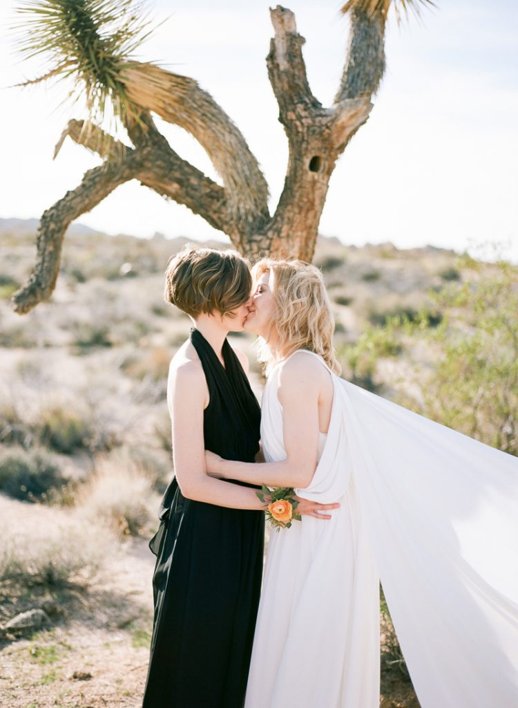 Desert elopement - intimate wedding in Joshua Tree. Two brides kiss after ceremony
