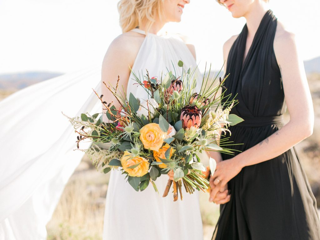 Joshua Tree elopement. Outdoor destination desert wedding with two brides. Organic floral bouquet.