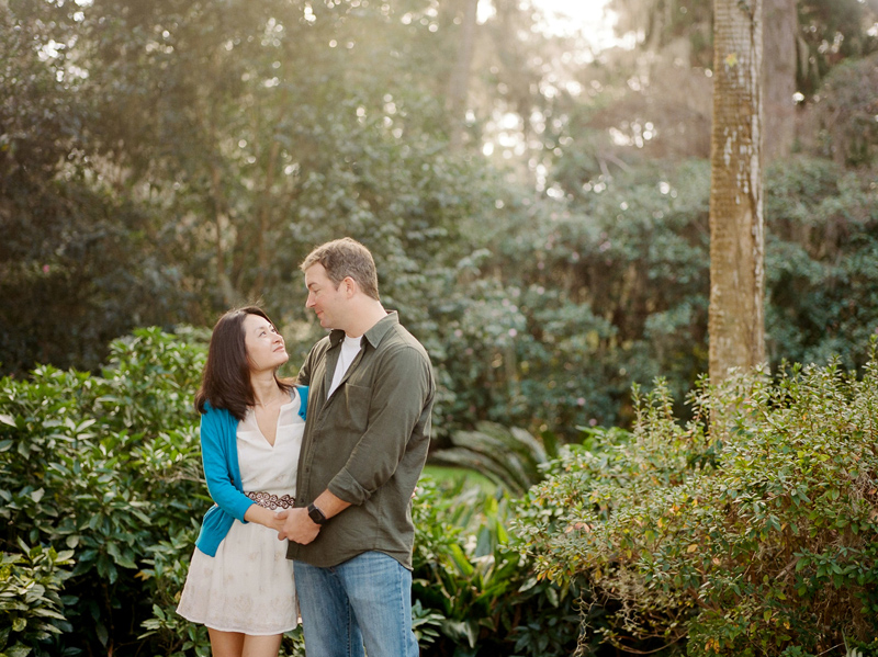 Romantic engagement photos in nature setting at botanical garden at sunset