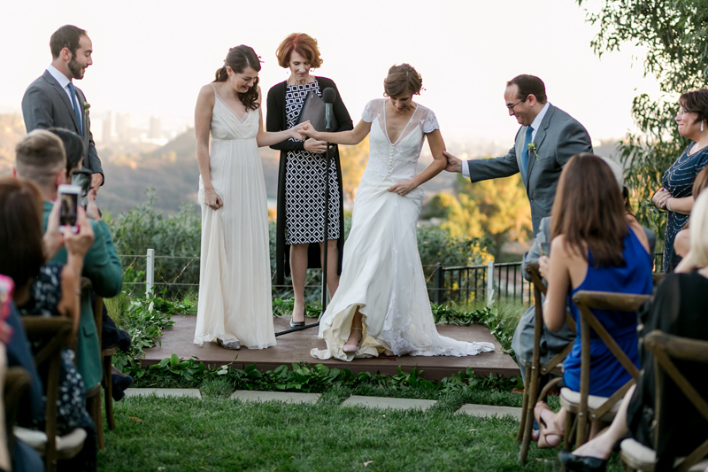 Two brides smash the glass at modern outdoor ceremony