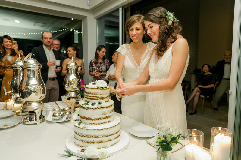 Brides cutting cake at Los Angeles LGBTQ at home wedding
